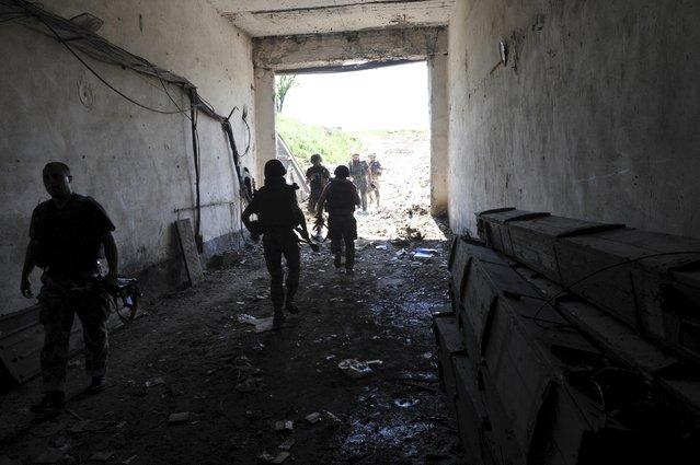 Members of the Ukrainian armed forces walk in the village of Pisky (Pesky) near the local airport, outside Donetsk, Ukraine, June 5, 2015. REUTERS/Oleksandr Klymenko