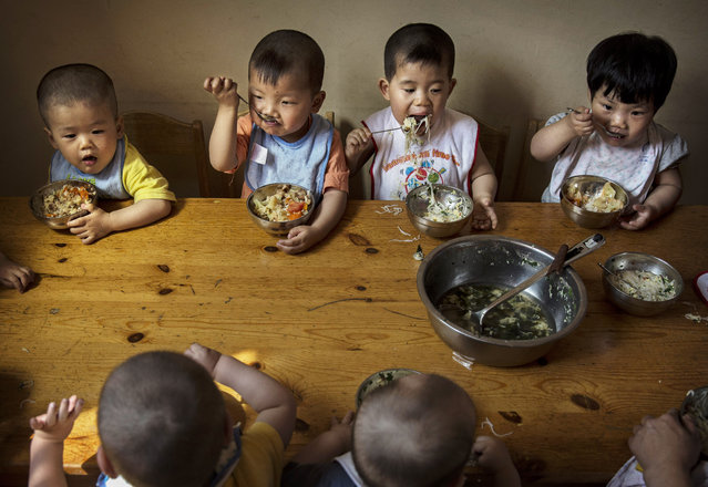 Young orphaned Chinese children eat a meal during feeding at a foster care center on April 2, 2014 in Beijing, China. China's orphanages and foster homes used to be filled with healthy girls, reflecting the country's one-child policy and its preference for sons. Now the vast majority of orphans are sick or disabled. China says it has 576,000 orphans in its child welfare system though outside groups put the number at closer to a million. (Photo by Kevin Frayer/Getty Images)