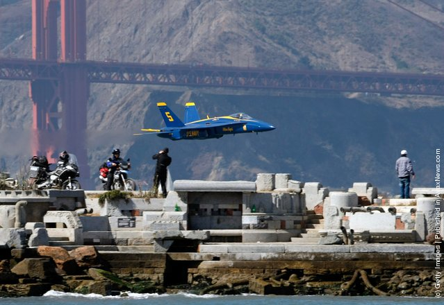 A U.S. Navy Blue Angels F/A-18 Hornet makes a low pass over San Francisco Bay during a practice session for San Francisco Fleet
