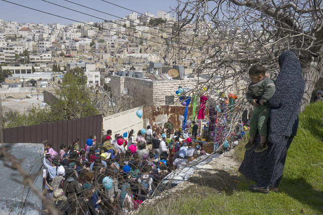 A Palestinian mother holds her son as they watch from their house as Jews pass by during the annual Purim parade in the predominantly Jewish sector of the West Bank city of Hebron, 12 March 2017. (Photo by Jim Hollander/EPA)