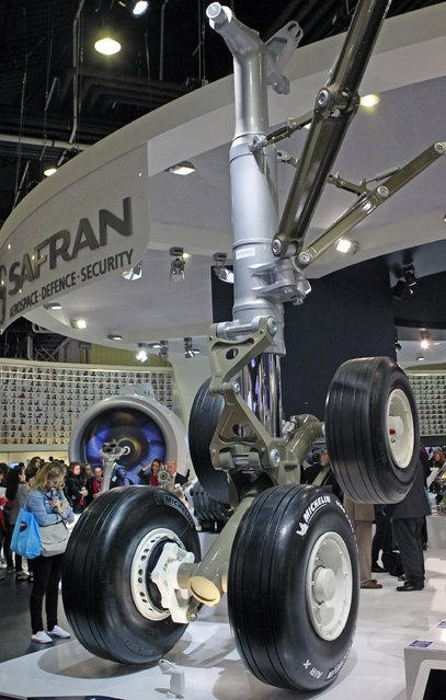 Visitors look at the Safran made landing gear of an Airbus A350, at the Paris Air Show in Le Bourget, north of Paris, Thursday June 18, 2015. Some 300,000 aviation professionals and spectators are expected at this week's Paris Air Show, coming from around the world to make business deals and see dramatic displays of aeronautic prowess and the latest air and space technology. (AP Photo/Remy de la Mauviniere)