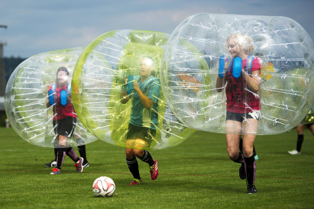 Players perform during a game at the first Bubble Soccer tournament in Hitzkirch, near Lucerne, Switzerland, June 27, 2015. Bubble Soccer, also known as Zorb Soccer, is becoming increasingly popular around the world. The game is a recreation of playing soccer whilst encased in an inflated zorb which covers the players upper-body and head. (Photo by Urs Flueeler/EPA)