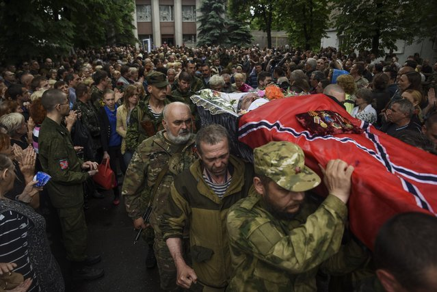 Pro-Russia rebels carry a coffin with the body of prominent separatist commander Alexei Mozgovoi during his funeral in Alchevsk, Ukraine, Wednesday, May 27, 2015. Alexei Mozgovoi and at least six other people were killed on Saturday in eastern Ukraine when his vehicle was ripped apart by a bomb and then strafed by gunfire. (Photo by Mstyslav Chernov/AP Photo)