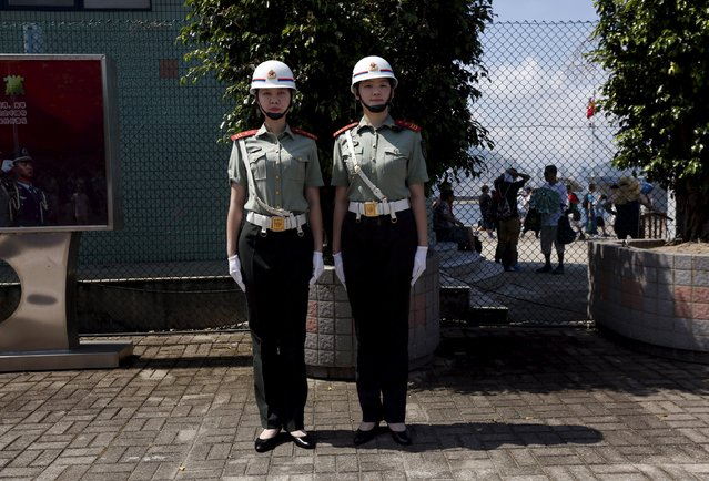 Two female People's Liberation Army (PLA) soldiers stand at attention at a PLA naval base in Hong Kong, China July 1, 2015. (Photo by Bobby Yip/Reuters)