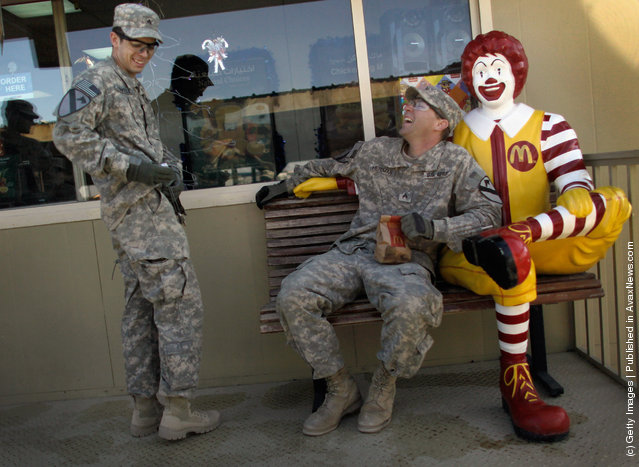 U.S. Army Sergeant James Linville from Brandon, Florida and Justin Herdman from Dover, Arkansas of the 2-82 Field Artillery, 3rd Brigade, 1st Cavalry Division, relax as they order McDonald's meals after arriving in Kuwait from Camp Adder in Iraq