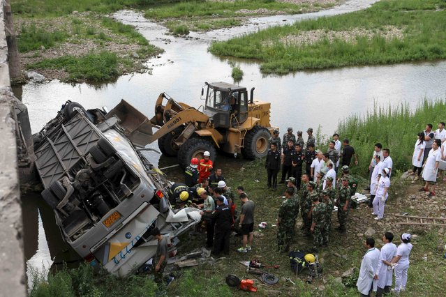 Rescue workers search at the site of a traffic accident, where a bus fell off a bridge, in Ji'an, Jilin province, China, July 1, 2015. According to Xinhua News Agency, at least nine people, including seven South Korean tourists, were killed in the accident Wednesday. The bus carrying 28 people, 26 of them South Koreans, was on its way from Ji'an to Dandong. (Photo by Reuters/Xinhua)