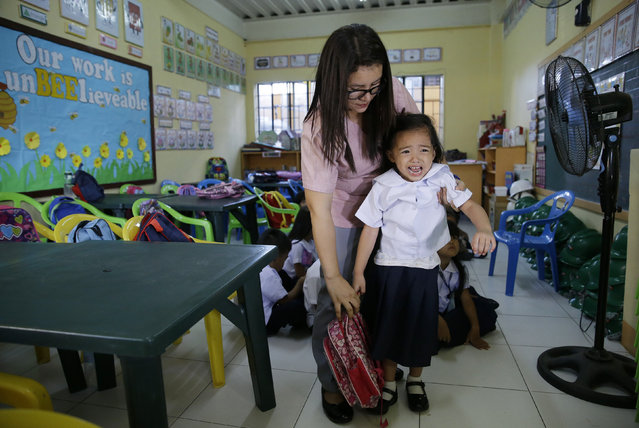A Filipino teacher tries to prevent a crying student from getting out of the classroom during the first day of school at the President Corazon C. Aquino Elementary School in metropolitan Manila, Philippines on Monday, June 3, 2019. About 27 million students are expected to troop back to schools amid perennial problems like overcrowded classrooms and lack of teachers and desks. (Photo by Aaron Favila/AP Photo)