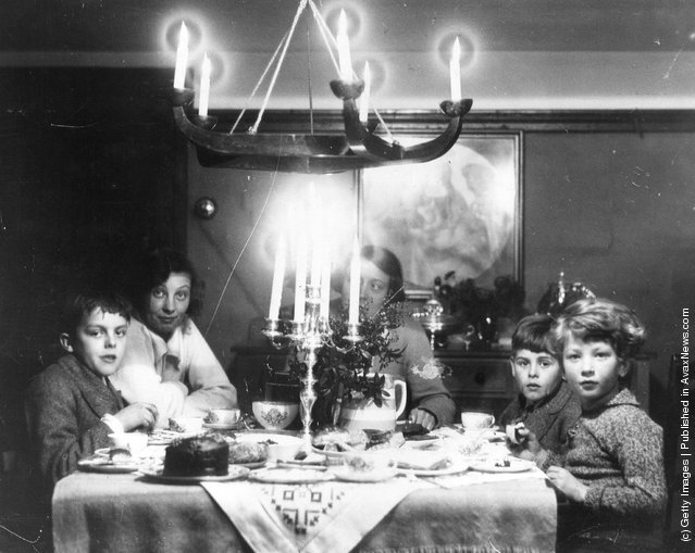 1935: A family at Christmas tea time with chocolate cake, a candelabra and holly on the table