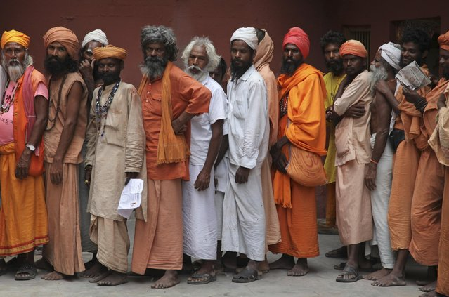 Hindu holy men line up to register for the annual pilgrimage to the Himalayan cave shrine Amarnath, in Jammu, India, Tuesday, June 30, 2015. More than half a million devotees make the annual pilgrimage to the shrine, an icy stalagmite in a mountain cave 4,115 meters (13,500 feet) above sea level. It is accessible only for about five weeks in high summer. Pilgrims make the trek on foot or on horseback, or are carried up the steep path by porters. (Photo by Channi Anand/AP Photo)