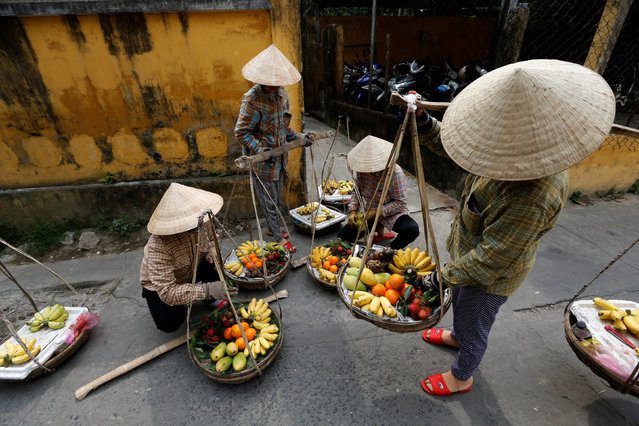 Women wearing traditional hats, known as a non la, sell fruits in Hoi An, Vietnam April 4, 2016. (Photo by Jorge Silva/Reuters)