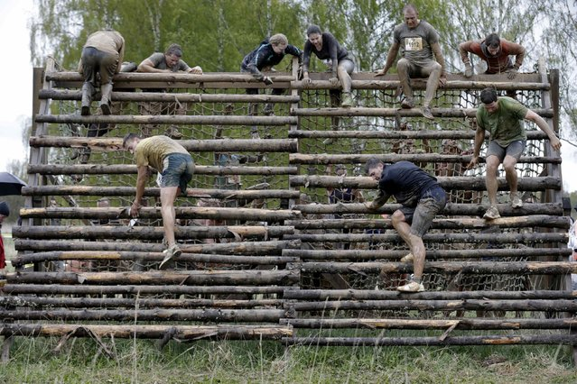 Participants cross obstacles during the Strong Race competition near Tukums May 4, 2014. (Photo by Ints Kalnins/Reuters)