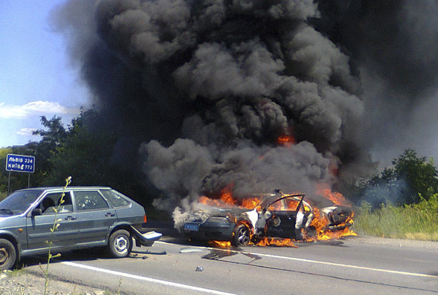 Two police cars on fire are seen at the site of unrest in Mukhachevo, Western Ukraine,  Saturday, July 11, 2015. (Photo by AP Photo)