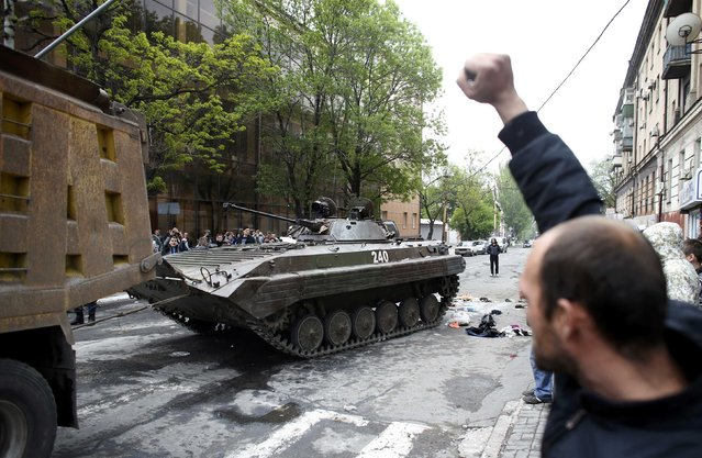 A man celebrates as a broken armoured vehicle left behind by Ukrainian forces is taken away by  pro-Russian militants in Mariupol May 9, 2014. Ukrainian security forces killed about 20 pro-Russian rebels who tried to seize control of police headquarters in the eastern port city of Mariupol on Friday, the Interior Minister said. (Photo by Marko Djurica/Reuters)