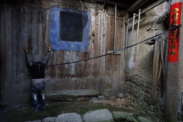 Xie Guobiao, 11, is tied to a pillar with a rope at his home in Daohui village of Lishui, Zhejiang province May 7, 2014. (Photo by William Hong/Reuters)