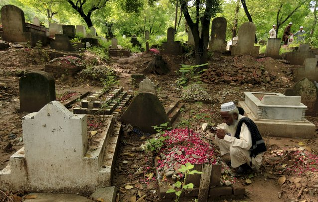 A man reads the Koranic supplication at the graves of his relatives at a cemetery, on the first day of Eid al-Fitr, which marks the end of the holy month of Ramadan, in Rawalpindi, Pakistan, July 18, 2015. (Photo by Faisal Mahmood/Reuters)