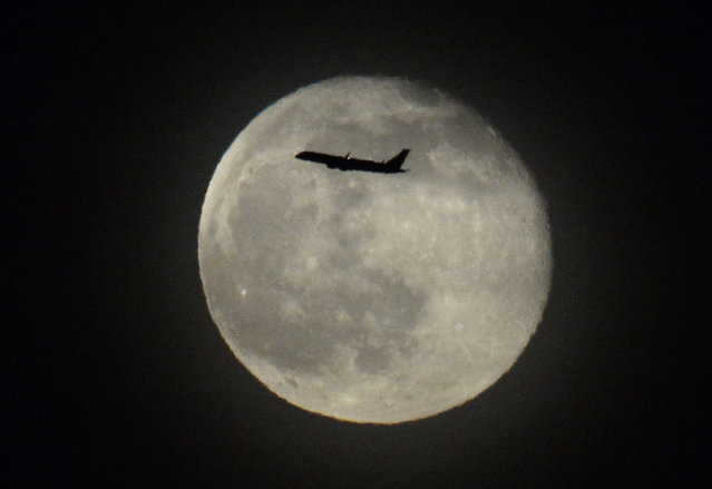 A jetliner takes off from San Francisco International Airport in front a full moon over San Francisco Bay in San Francisco, California, USA, 15 May 2014. (Photo by John G. Mabanglo/EPA)
