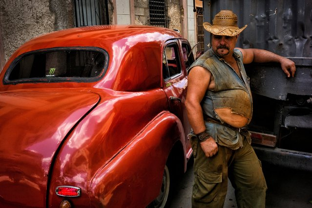 "A worker rests against his truck after a delivery as a 1950s Peugeot passes by in a busy street of Old Havana, Cuba, May 3, 2016. Saguy writes, ""The decal on the back of the classic car is no anomaly; many cars in Cuba proudly display the decals of American brands such as Apple or Monster Energy drinks"". (Photo by Dotan Saguy)"