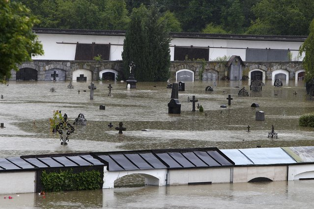Gravestones are partially submerged by flood water at a cemetery in Schaerding, Upper Austria June 3, 2013. REUTERS/Michaela Rehle