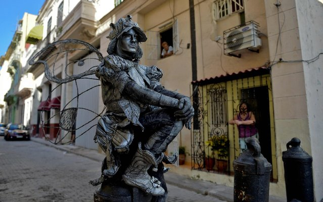 Cuban Beatriz Estevez, 29, performs as a human statue in the streets of Havana on October 15, 2019. Estevez dropped out of law school and found her personal and economic fulfillment in art. Daughter of a naval engineer, Beatriz earns in one day what her father earns in a month of work for the Cuban state. Havana residents say the Malecon -esplanade along the waterfront- is their sofa, and that he who sits there looking to the water is sad, and he who looks to the city is happy. Their stories build a 500-year-old Havana. (Photo by Yamil Lage/AFP Photo)