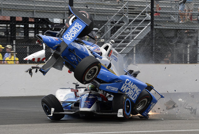 The car driven by Scott Dixon, of New Zealand, goes over the top of Jay Howard, of England, in the first turn during the running of the Indianapolis 500 auto race at Indianapolis Motor Speedway, Sunday, May 28, 2017, in Indianapolis. (Photo by Marty Seppala/AP Photo)