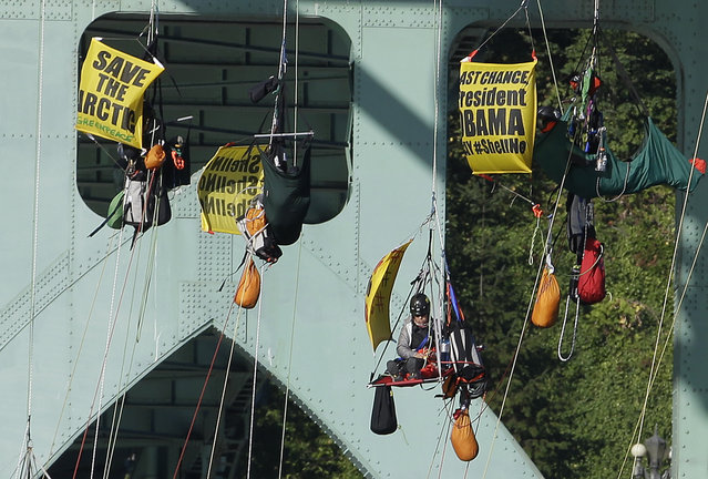 Activists hang from the St. Johns bridge in Portland, Ore., Wednesday, July 29, 2015, to protest  the departure of Royal Dutch Shell PLC icebreaker Fennica, which is in Portland for repairs. (Photo by Don Ryan/AP Photo)
