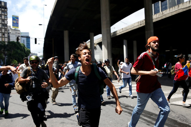 A demonstrator shouts slogans as they run during a protest called by university students against Venezuela's government in Caracas, Venezuela, June 9, 2016. (Photo by Carlos Garcia Rawlins/Reuters)