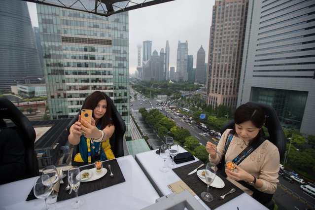 "Diners are suspended from a crane as they enjoy a meal organized by the ""Dinner in the Sky"" over Lujiazui Financial District in Shanghai on June 27, 2014. Dinner in the Sky kicked off in Shanghai on June 27 with 22 diners enjoying their meal in a sky box suspended from a crane about 50 meters above the ground, at a price that varies from 1,888 yuan (302 USD) to 8,888 yuan (1,423 USD). (Photo by AFP Photo/Stringer)"