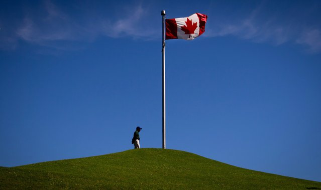 A man pauses on top of a hill to take in the view as a Canadian flag flies in the wind at Granville Island in Vancouver, B.C., on Monday June 30, 2014. Canadians will mark the country's 147th birthday on Canada Day, Tuesday. (Photo by Darryl Dyck/The Canadian Press)