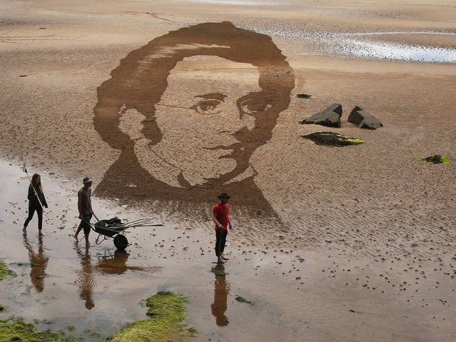(L to R) Claire Jamieson, Tom Bolland and Jamie Wardley from sand sculpture company Sand in Your Eye, creates a sculpture of Franz Schubert on Elie Beach in Scotland, on June 30, 2014. (Photo by Danny Lawson/PA Wire)