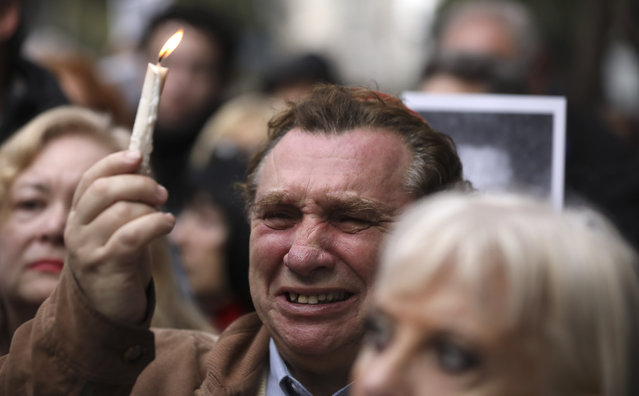 A man cries as he holds up a candle on the 25th anniversary of the bombing of the AMIA Jewish center that killed 85 people in Buenos Aires, Argentina, Thursday, July 18, 2019. (Photo by Natacha Pisarenko/AP Photo)