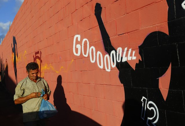"""A man walks past a graffiti near the entrance of Estadio Manoel Barradas stadium in Salvador June 30, 2014. In a project called """"On The Sidelines"""" Reuters photographers share pictures showing their own quirky and creative view of the 2014 World Cup in Brazil. (Photo by Yves Herman/Reuters)"""