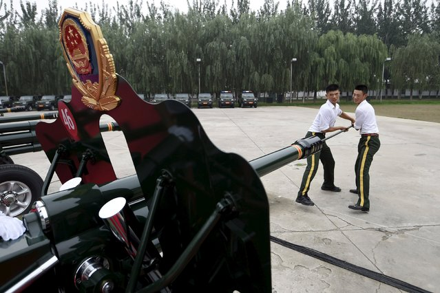 Paramilitary policemen and members of a gun salute team load cannons during a training session for a military parade to mark the 70th anniversary of the end of the World War Two, at a military base in Beijing, China, August 1, 2015. China will hold the parade on September 3. (Photo by Reuters/Stringer)