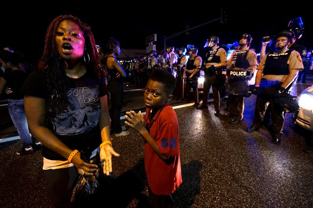 Amarion Allen, 11-years-old (C), and his mother Amima stand in front of a police line shortly before shots were fired in a police-officer involved shooting in Ferguson, Missouri August 9, 2015. Two people were shot in the midst of a late-night confrontation between riot police and protesters, after a day of peaceful events commemorating the fatal shooting of Michael Brown by a white officer one year ago. (Photo by Rick Wilking/Reuters)