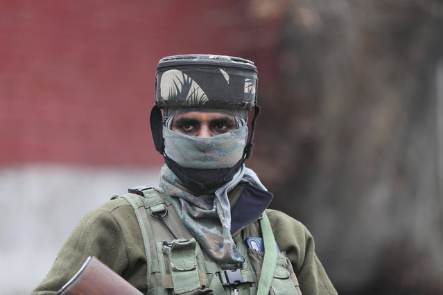 An Indian paramilitary soldier guards as a convoy of New Delhi-based diplomats passes through Srinagar, Indian controlled Kashmir, Thursday, January 9, 2020. Envoys from 15 countries including the United States are visiting Indian-controlled Kashmir starting Thursday for two days, the first by New Delhi-based diplomats since India stripped the region of its semi-autonomous status and imposed a harsh crackdown in early August. (Photo by Mukhtar Khan/AP Photo)
