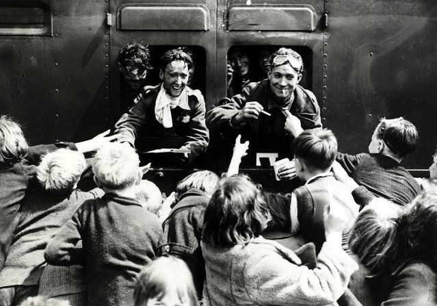 As the troop train pulls up at a London station, children rush to hand cigarettes, refreshments and food to the men of the British Expeditionary Force, returning after their evacuation from Dunkirk, Flanders during the World War Two, on May 31, 1940. As many as 300,000 Allied troops escaped certain death or capture to make it back to England. (Photo by Popperfoto/Getty Images)