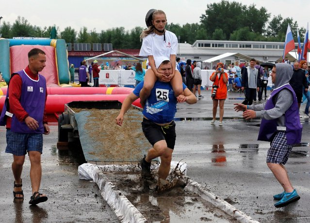 A man carries his wife over an obstacle while competing in the Wife Carrying Championship to mark City Day in Krasnoyarsk, Siberia, Russia, June 25, 2016. (Photo by Ilya Naymushin/Reuters)