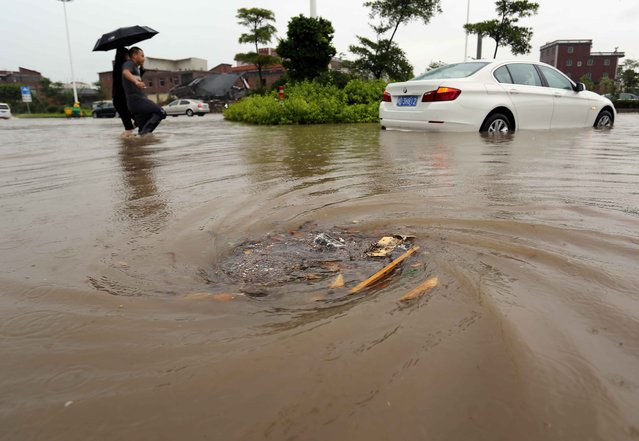 Floodwaters swirl into the sewer system in Jinjiang, south China's Fujian province of July 23, 2014 as typhoon Matmo makes landfall in China. Typhoon Matmo pounded Taiwan with fierce winds and downpours, leaving nine people injured, shuttering financial markets, and interrupting rail and air transportation. (Photo by AFP Photo)