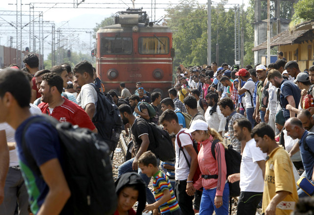 Migrants cross the raiway tracks in front of a train entering the railway station in the southern Macedonian town of Gevgelija, on Saturday, August 15, 2015. Macedonia is a major transit route for thousands of migrants from Middle East, Asia and Africa who are heading north through the Balkans on their way to the more prosperous European Union countries. (Photo by Boris Grdanoski/AP Photo)