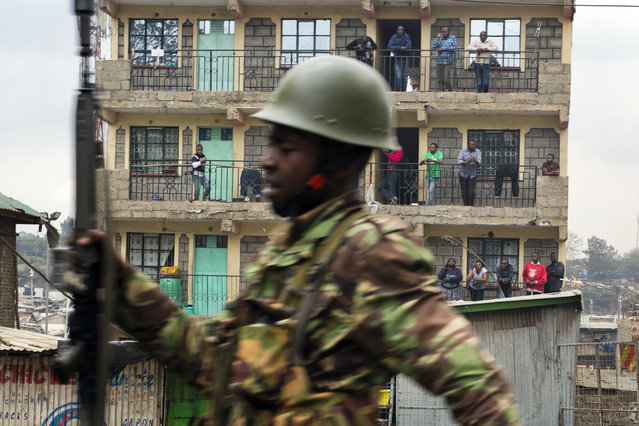 Residents watch from their balconies as Kenyan security forces chase supporters of Kenyan opposition leader and presidential candidate Raila Odinga who demonstrate in the Mathare area of Nairobi Wednesday August 9, 2017. (Photo by Jerome Delay/AP Photo)