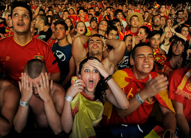 Spanish fans react while watching on a giant outdoor screen on Paseo de La Castellana street the UEFA EURO 2012 semi-final match between Spain and Portugal on June 27, 2012 in Madrid, Spain
