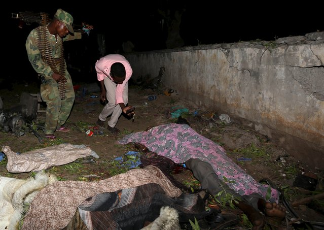 A Somali soldier looks at dead bodies of civilians who died after a suicide car bomb exploded near Juba hotel in capital Mogadishu August 22, 2015. At least 21 people were killed in two separate suicide car attacks in Somalia on Saturday, one in Mogadishu and another at a military training base in the southern port city of Kismayu, police and military sources said. (Photo by Feisal Omar/Reuters)