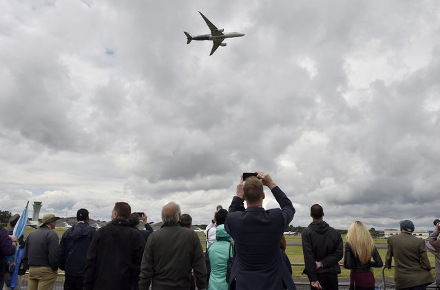 Plane enthusiasts watch an Airbus A350 during flight at the Farnborough International Airshow in Farnborough, Britain, 12 July 2016. (Photo by Hannah Mckay/EPA)