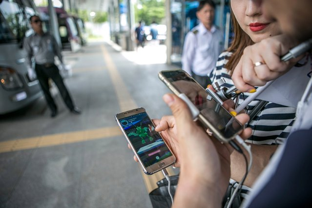 Lee Jeong-hwan (R) and Barbie Lim (second from right), broadcasting jockeys for Pokemon Go Korea Facebook page, broadcast live as Lee plays the game at the Express Bus Terminalon July 15, 2016 in Sokcho, South Korea. (Photo by Jean Chung/Getty Images)