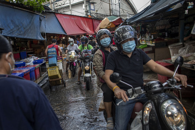 Thai people wearing protective masks ride through a wholesale market in Bangkok, Thailand, Wednesday, March 25, 2020. Thailand's government announced Tuesday it will declare an emergency later in the week allowing them to take stricter measures to control the coronavirus outbreak that has infected hundreds of people in the Southeast Asian country. (Photo by Gemunu Amarasinghe/AP Photo)