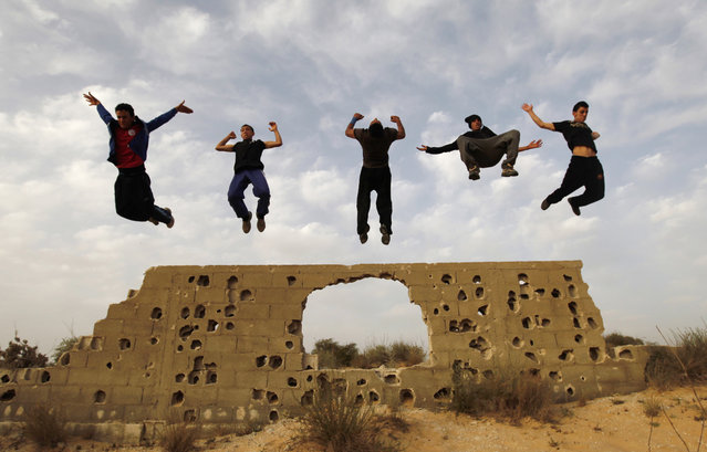 Palestinian youths practice their parkour skills in KhanYounis, southern Gaza Strip , Sunday, March 31, 2013. Parkour is a physical discipline of movement focused on overcoming obstacles. Training is held at cemeteries in KhanYounis. (Photo by Hatem Moussa/AP Photo)