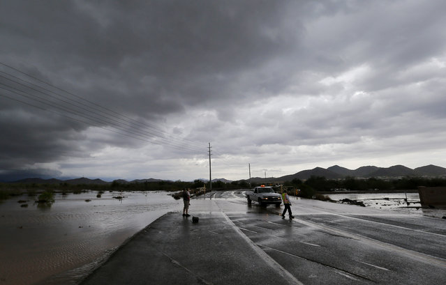 A city of Phoenix official blocks a closed section of road as flash flood waters overrun Skunk Creek through the Sonoran Desert, Tuesday, August 19, 2014, in northwestern Phoenix. Flooding from heavy rain in the Phoenix area has forced authorities to close several major roads, including a portion of Interstate 17 about 25 miles north of the city. (Photo by Matt York/AP Photo)