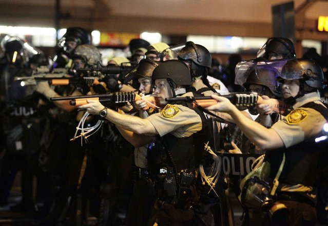 Police officers point their weapons at demonstrators protesting against the shooting death of Michael Brown in Ferguson, Missouri August 18, 2014. Police fired tear gas and stun grenades at protesters on Monday after days of unrest sparked by the fatal shooting of unarmed black teenager Michael Brown by a white policeman. (Photo by Joshua Lott/Reuters)