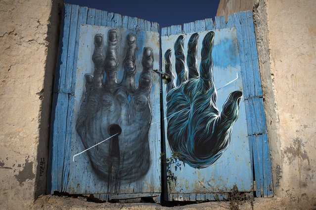 """A mural by French artist BOM-K decorates a wall in the village of Erriadh, on the Tunisian island of Djerba, on August 7, 2014, as part of the artistic project """"Djerbahood"""". (Photo by Joel Saget/AFP Photo)"""