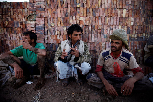 A labourer plays a flute as other labourers listen at a brick factory on the outskirt of Sanaa, Yemen, June 5, 2016. (Photo by Mohamed al-Sayaghi/Reuters)