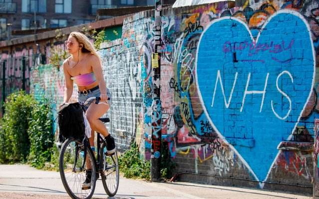 A cyclist rides past graffiti paying tribute to NHS workers in east London on April 24, 2020 during the national lockdown due to the novel coronavirus COVID-19 pandemic. (Photo by Tolga Akmen/AFP Photo)
